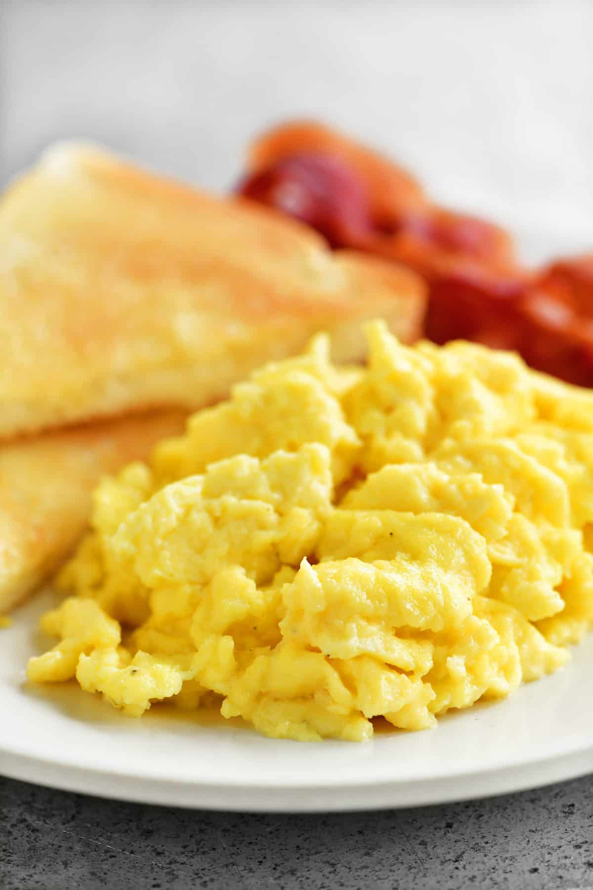 a delicious helping of scrambled eggs with bacon and toast