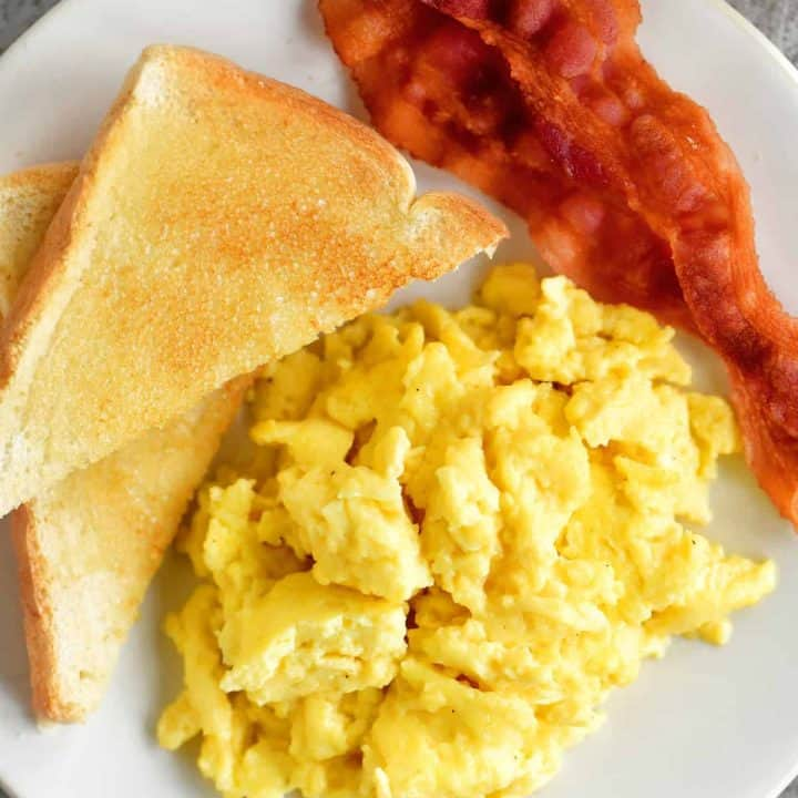 a topdown view of scrambled eggs, toast and bacon