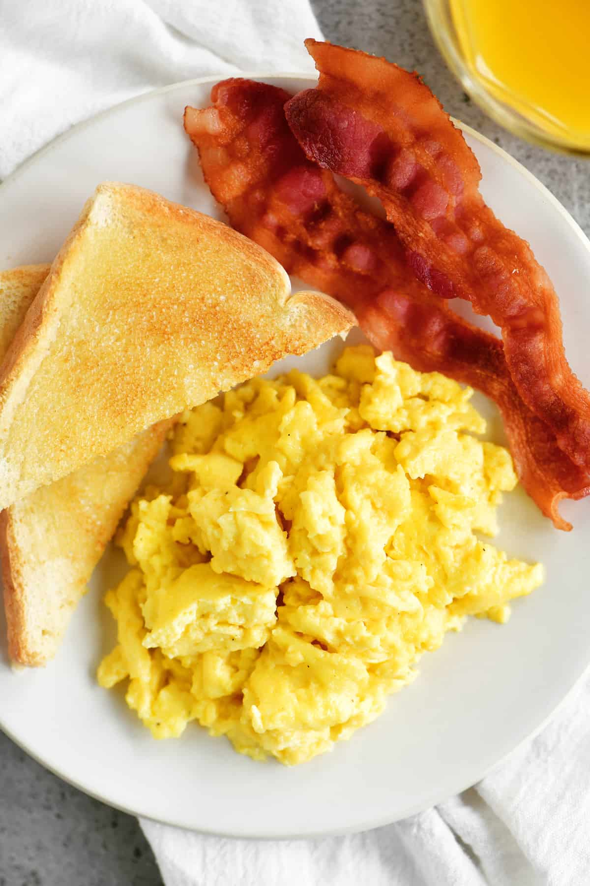 scrambled eggs, bacon and toast on a plate