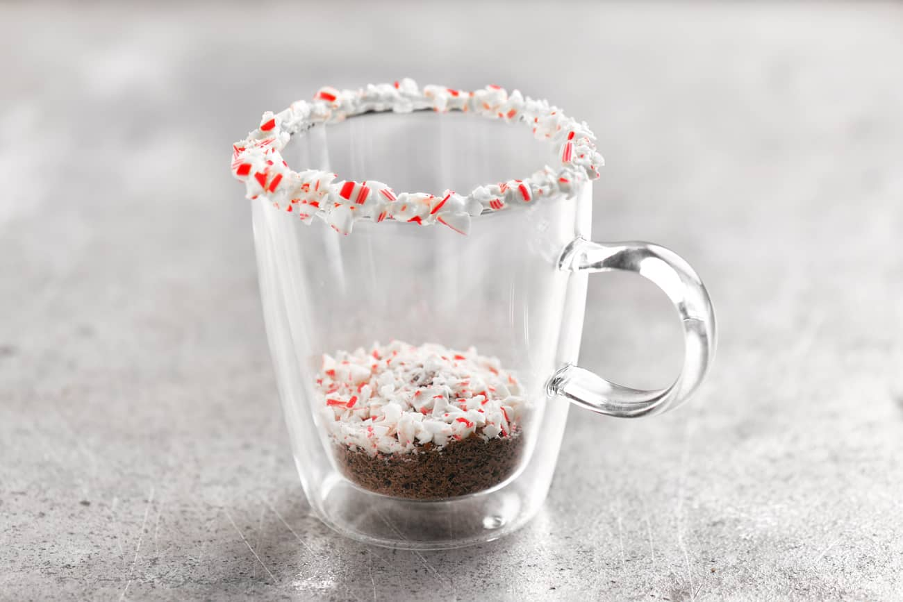 adding crushed candy cane pieces to the coffee drink