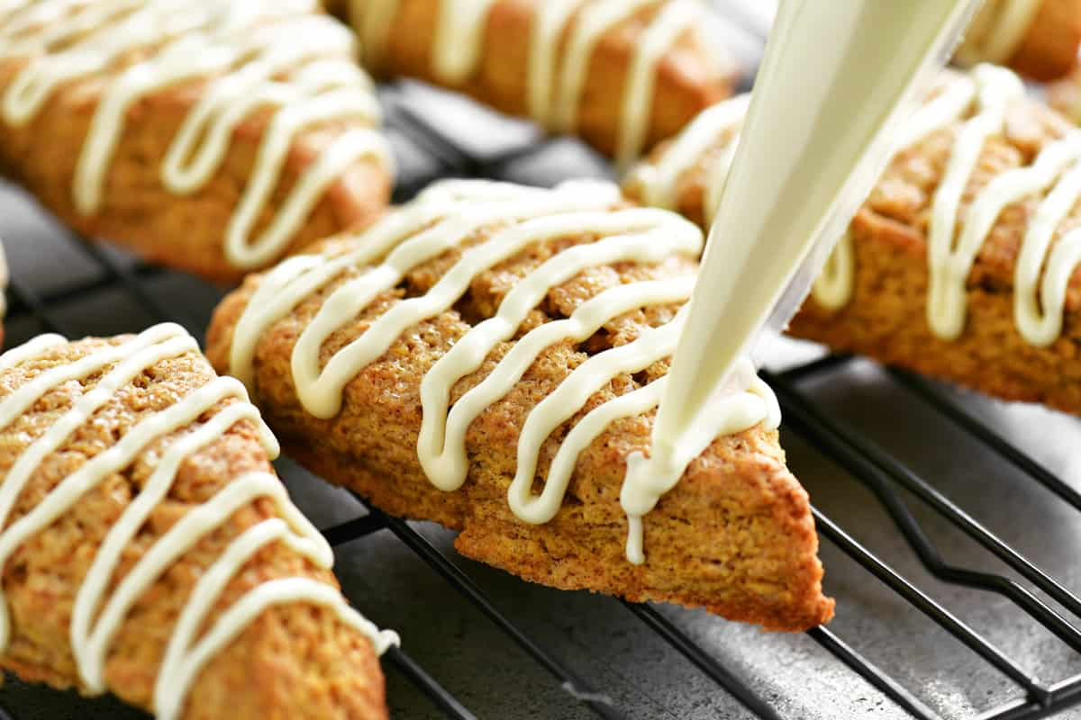 piping frosting onto the scones
