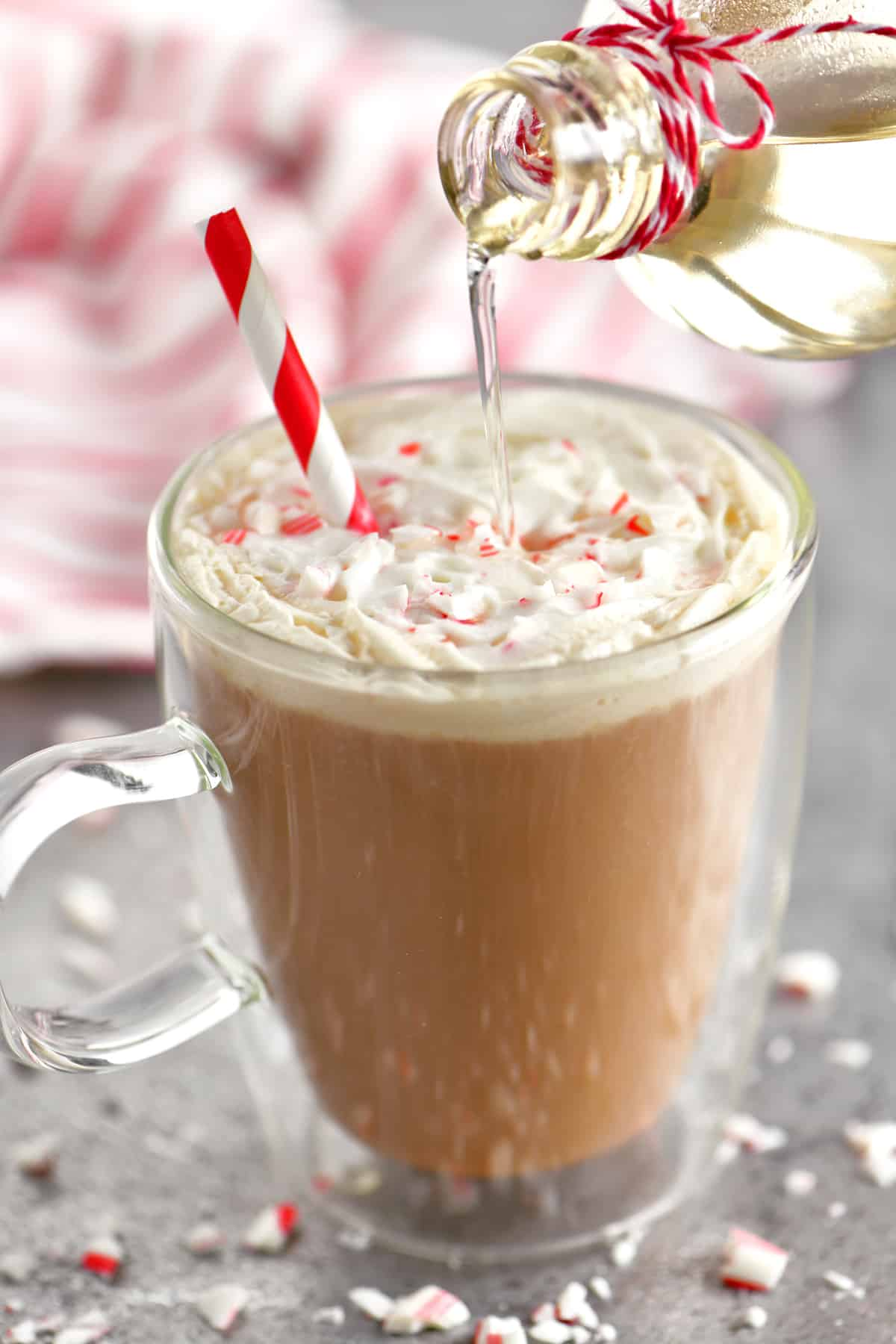 pouring the peppermint syrup into the whipped mocha drink