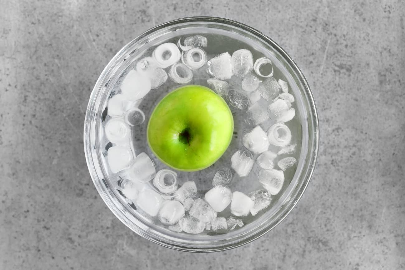 a photo of a green apple in a bowl of ice water