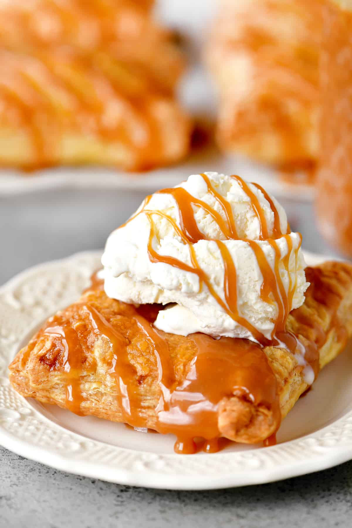 a delectable piece of Caramel Apple dessert with vanilla ice cream and caramel on top