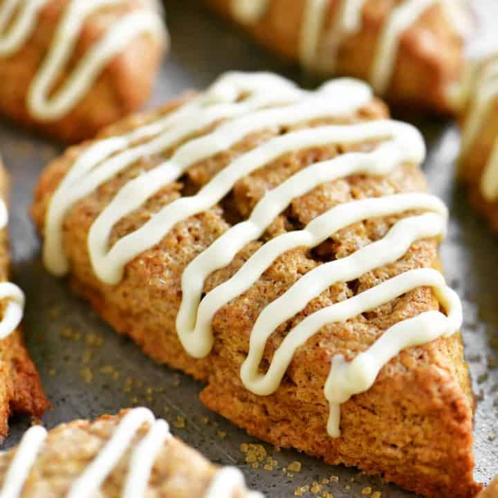 a close-up of a pumpkin scone with white glaze drizzled on top