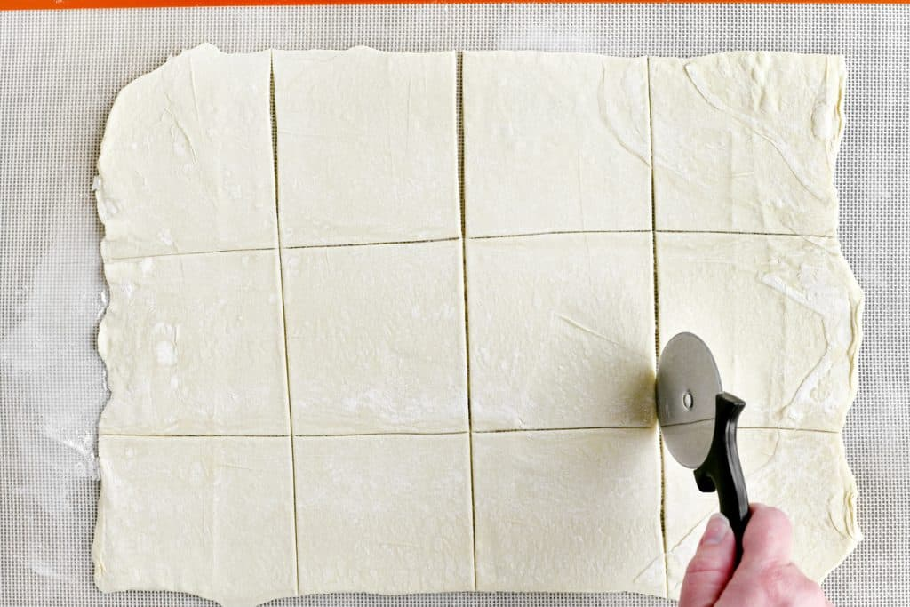 cutting the dough with a pizza cutter