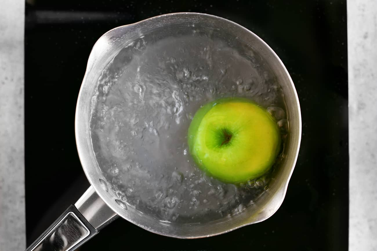 a photo of a green apple in a pot of boiling water