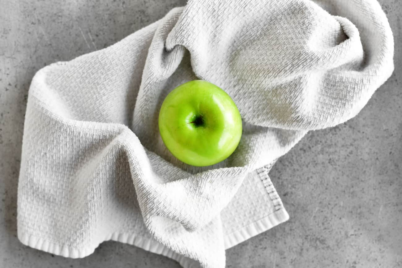 a photo of a green apple on a textured towel