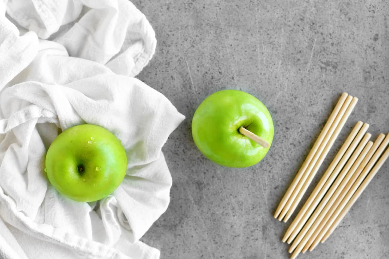 a photo showing the process step of inserting a stick into an apple