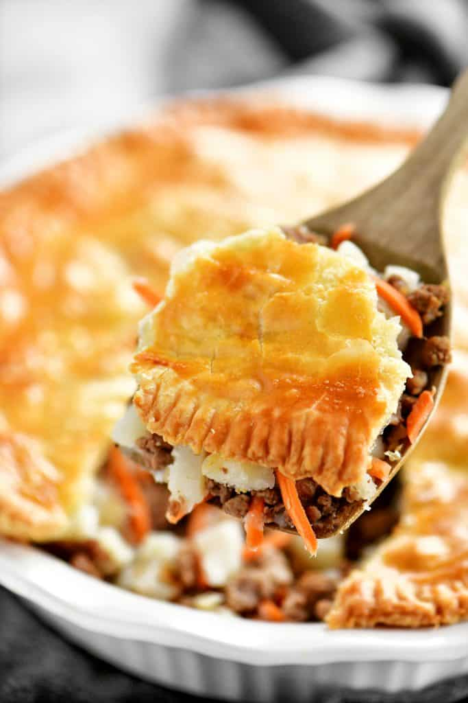 a serving of meat pie on a wooden spoon