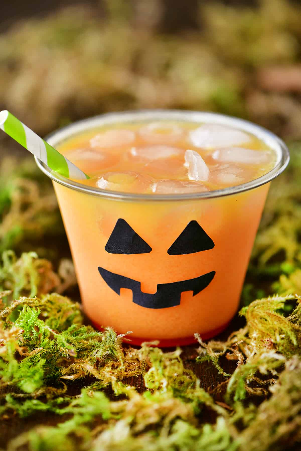 a photo of an orange Halloween drink with a jack-o-lantern theme