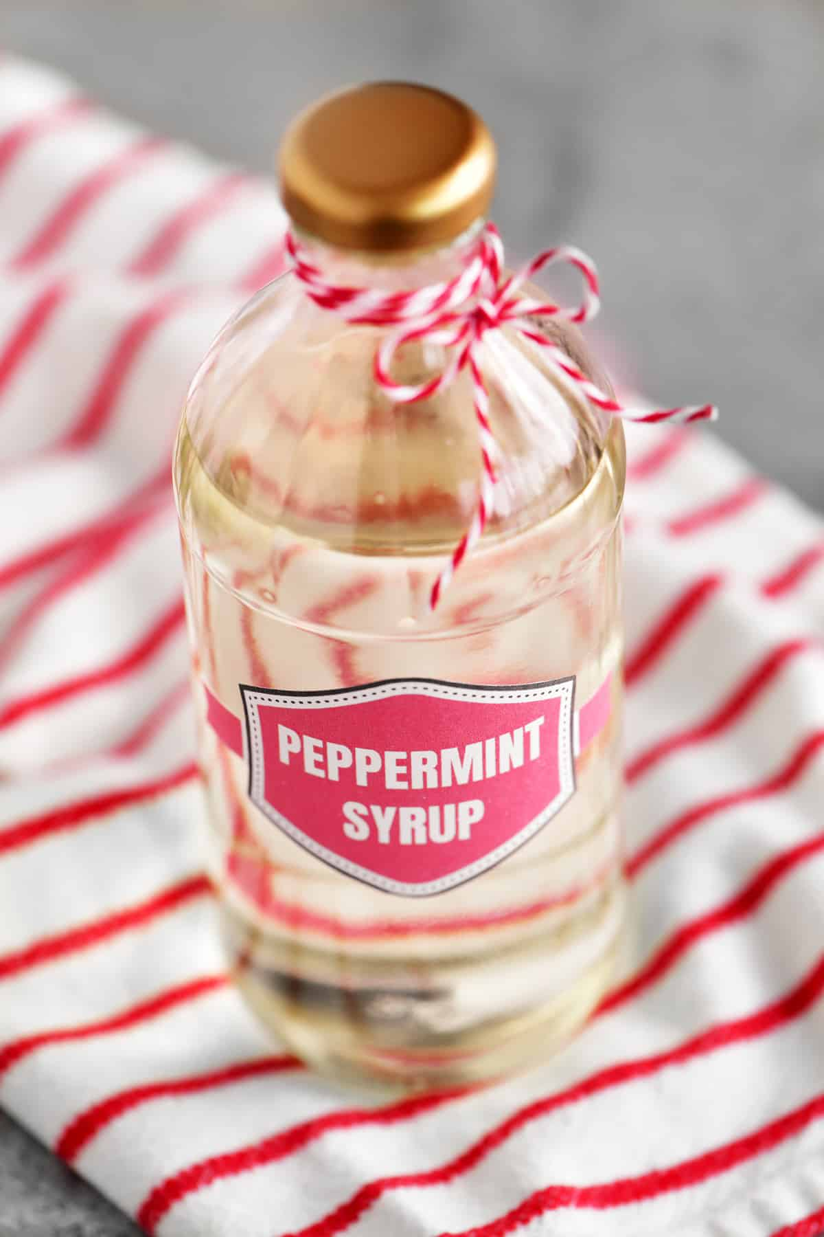 a bottle of peppermint syrup on a red and white striped towel