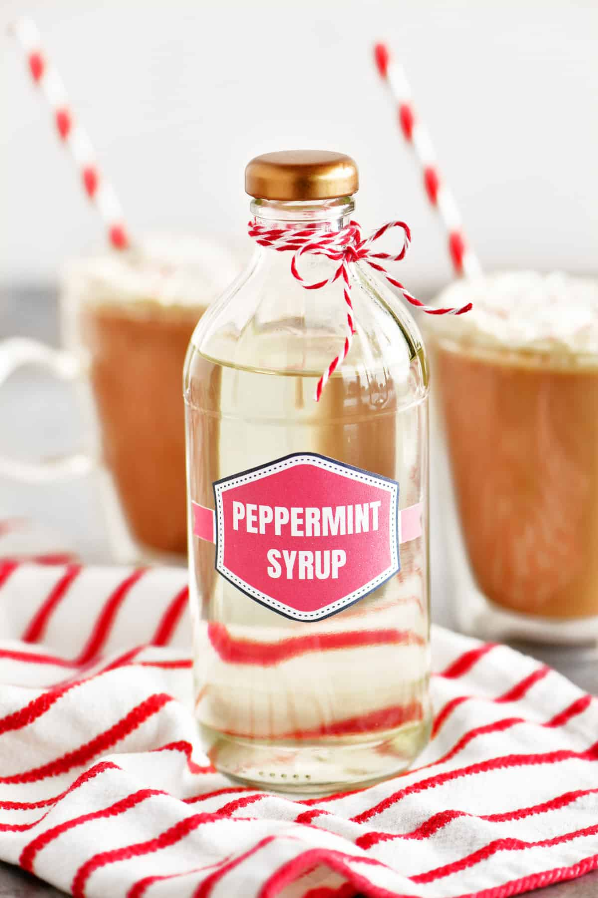 a photo of a bottle of peppermint coffee syrup with some mocha drinks in the background