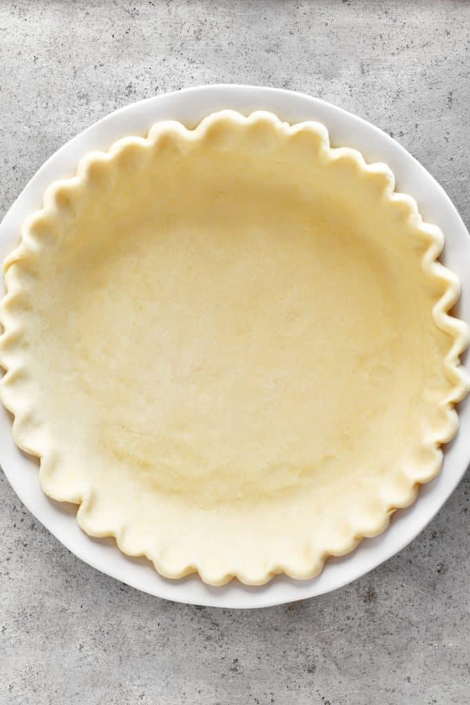 unbaked pie crust in white ceramic pie plate
