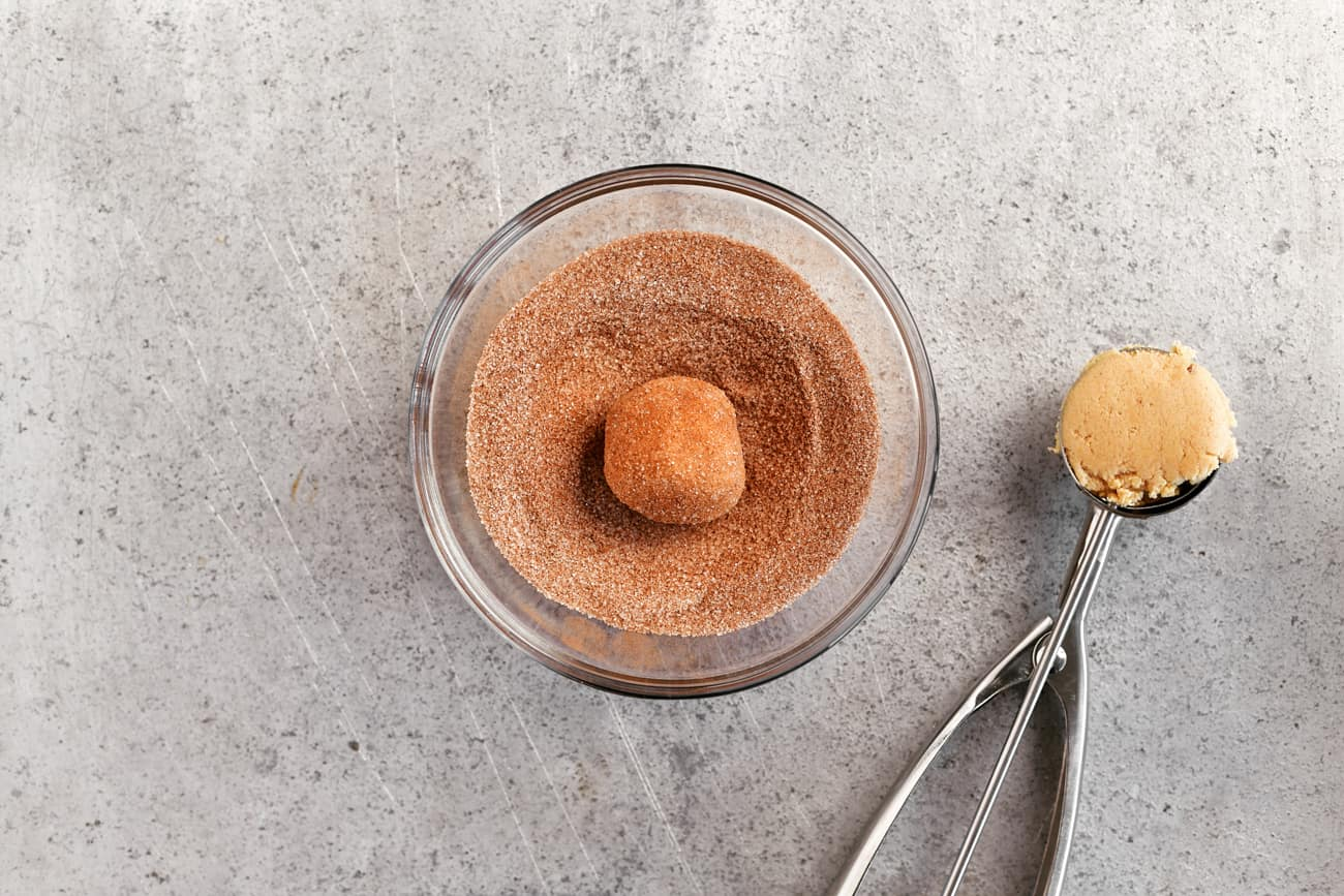 scooping the dough and coating with cinnamon sugar