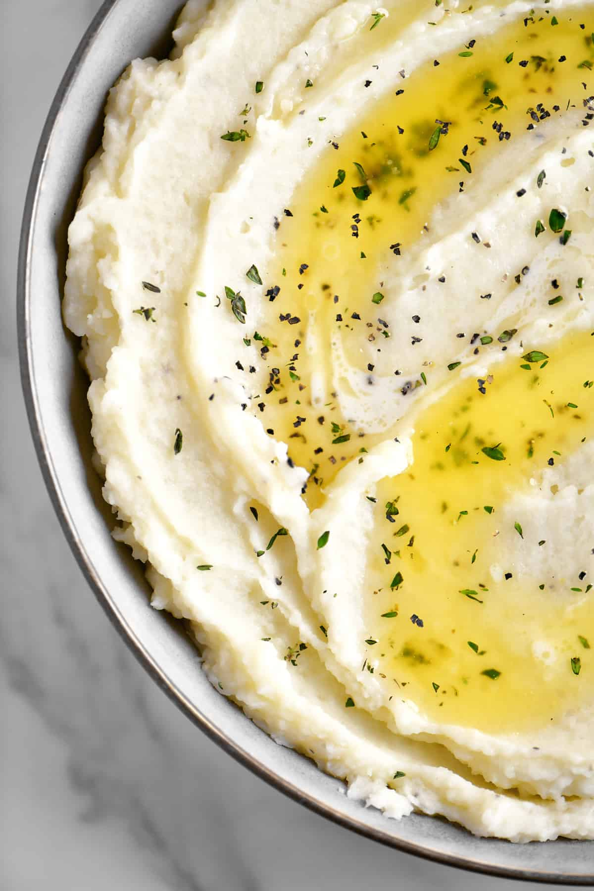 a close-up topdown photo of garlic flavored mashed potatoes in a bowl