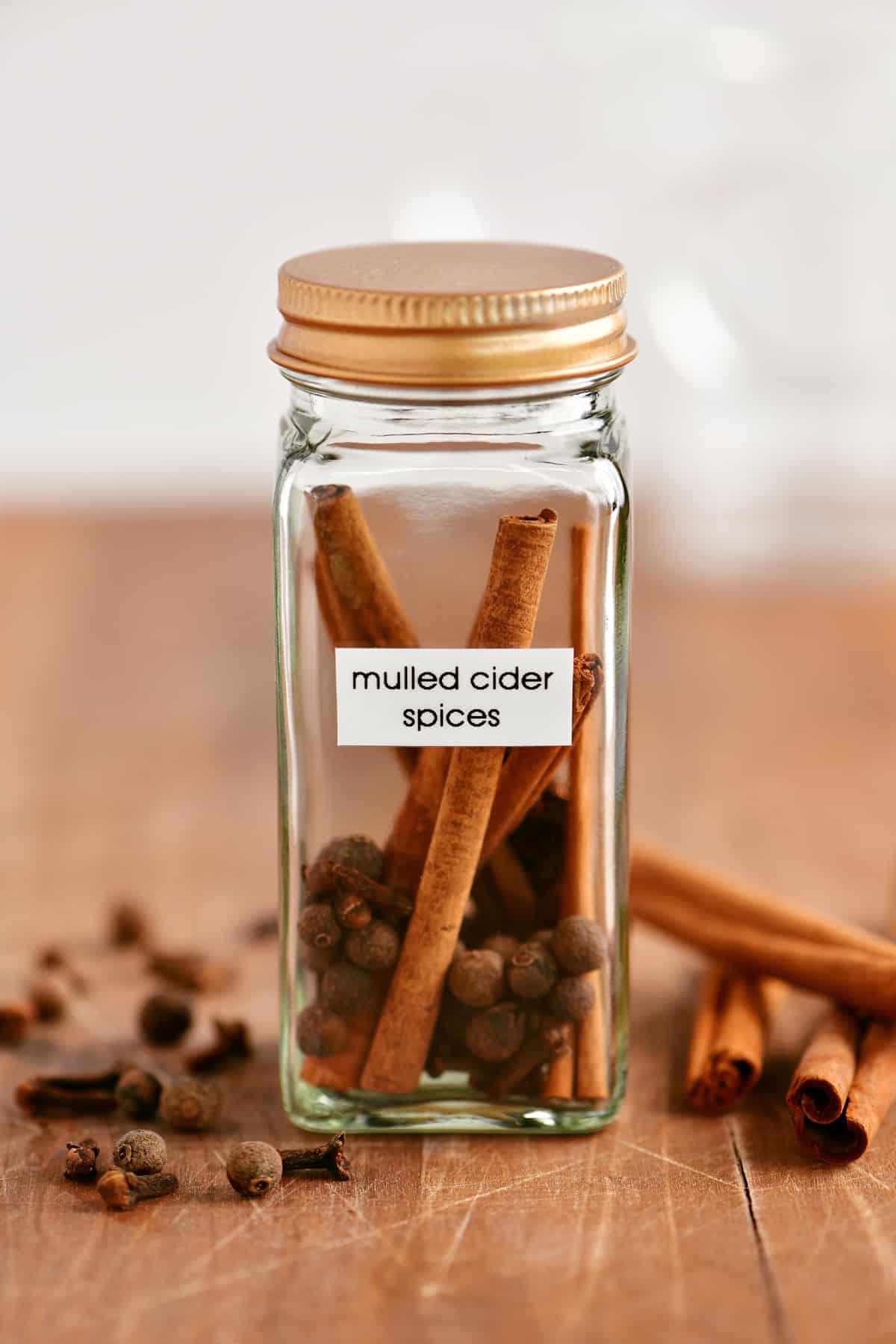 cinnamon sticks, cloves, and allspice in a glass jar