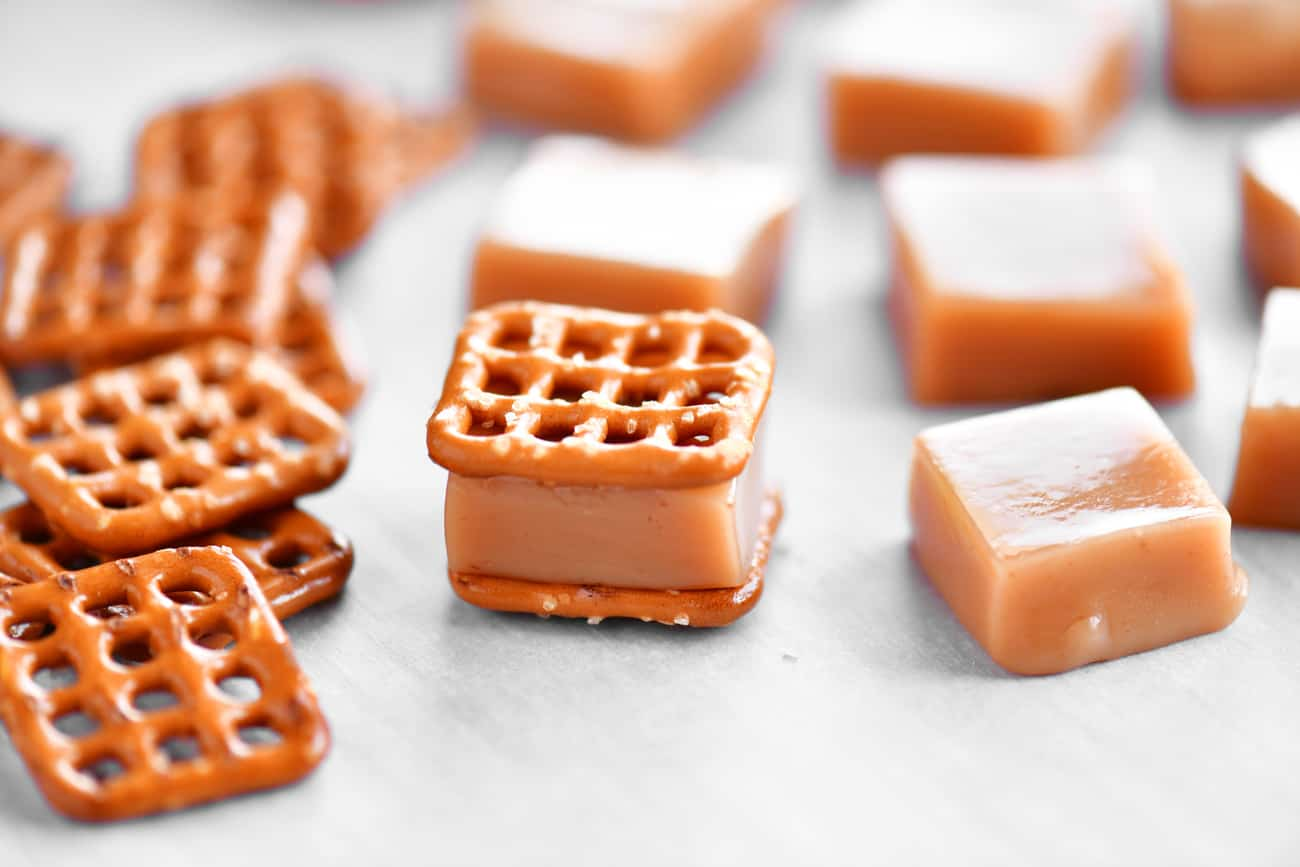 adding bite size pretzel squares to the caramels