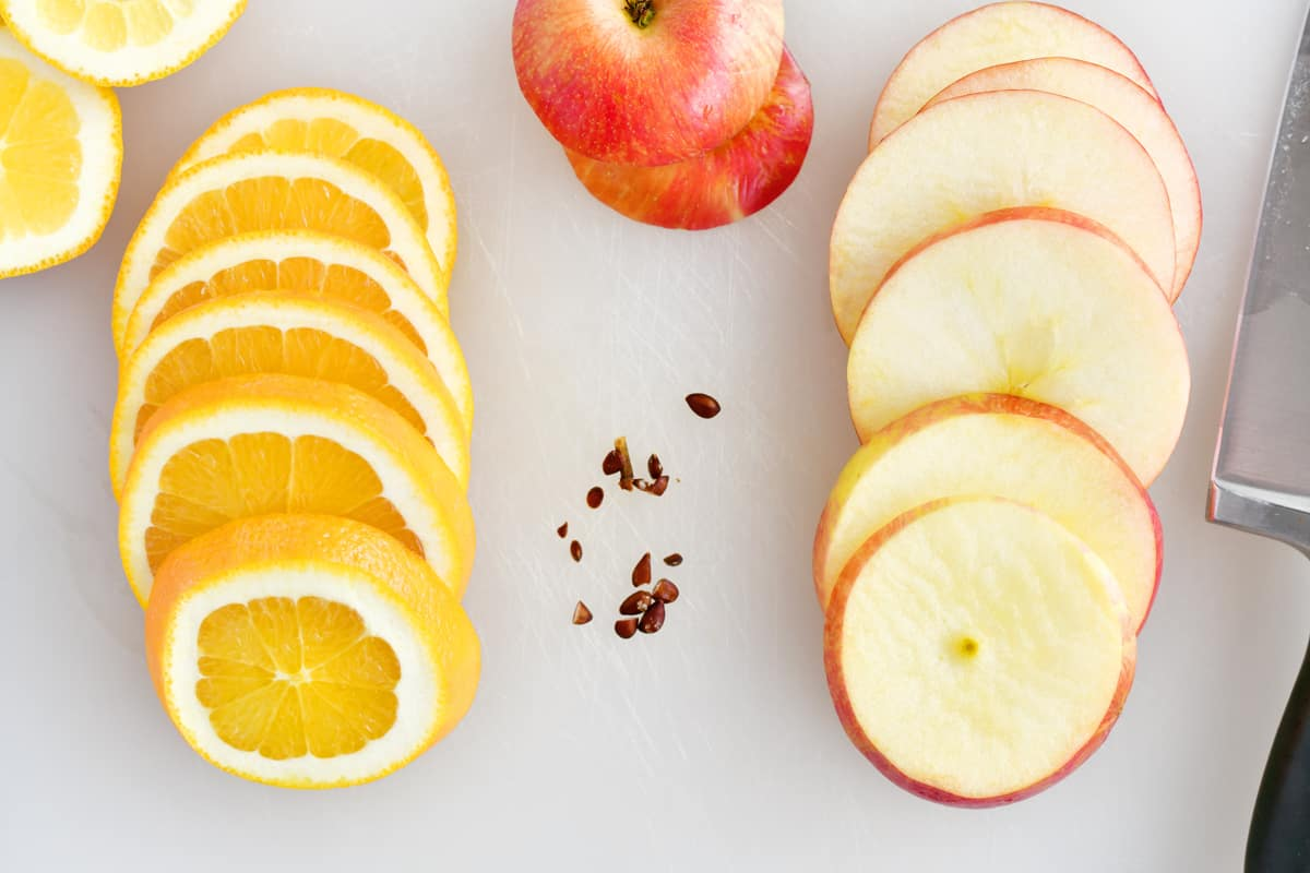 sliced apple and orange on cutting board