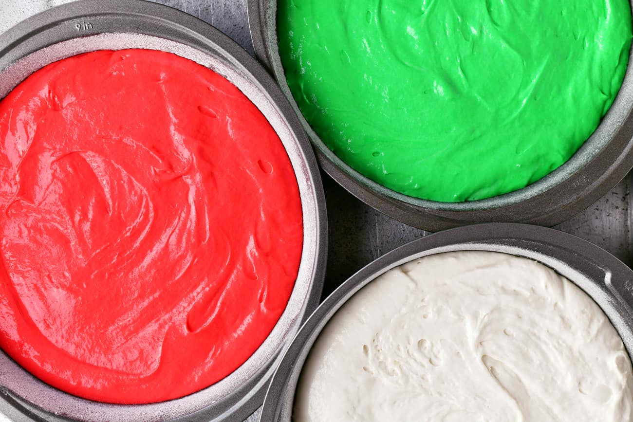 pouring the dyed batter into cake pans