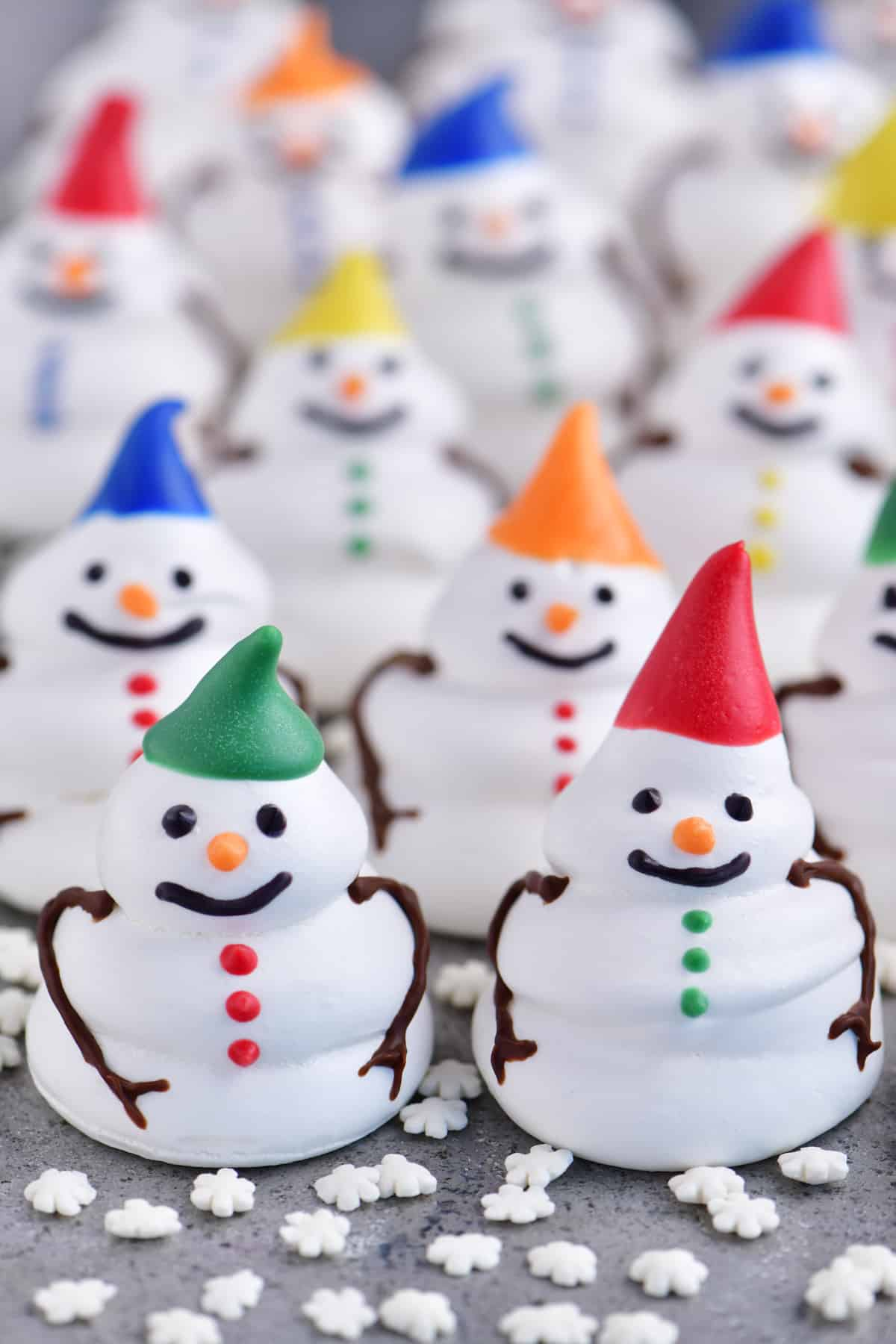 a photo of several meringue snowman cookies with colorful hats and buttons