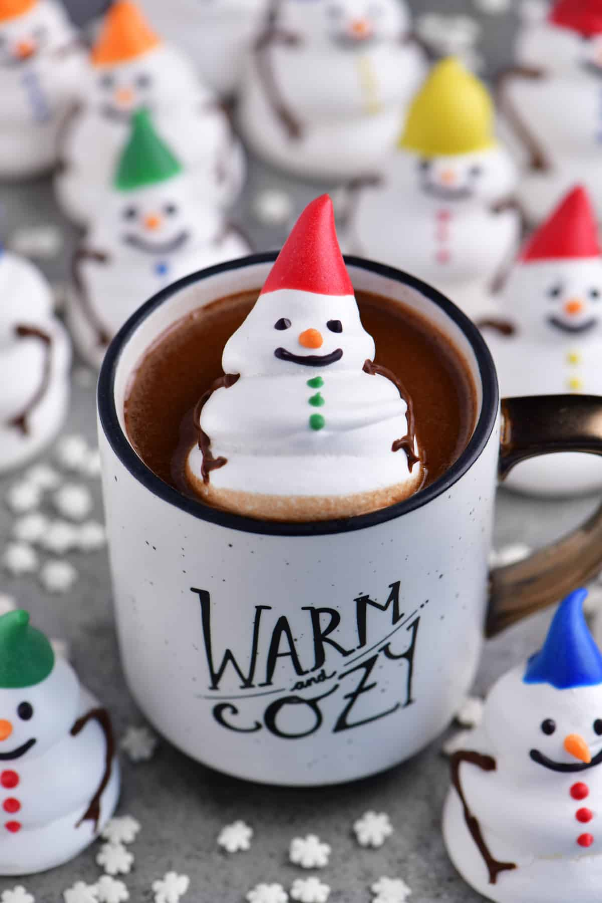 a snowman meringue cookie floating in a cup of delicious hot chocolate