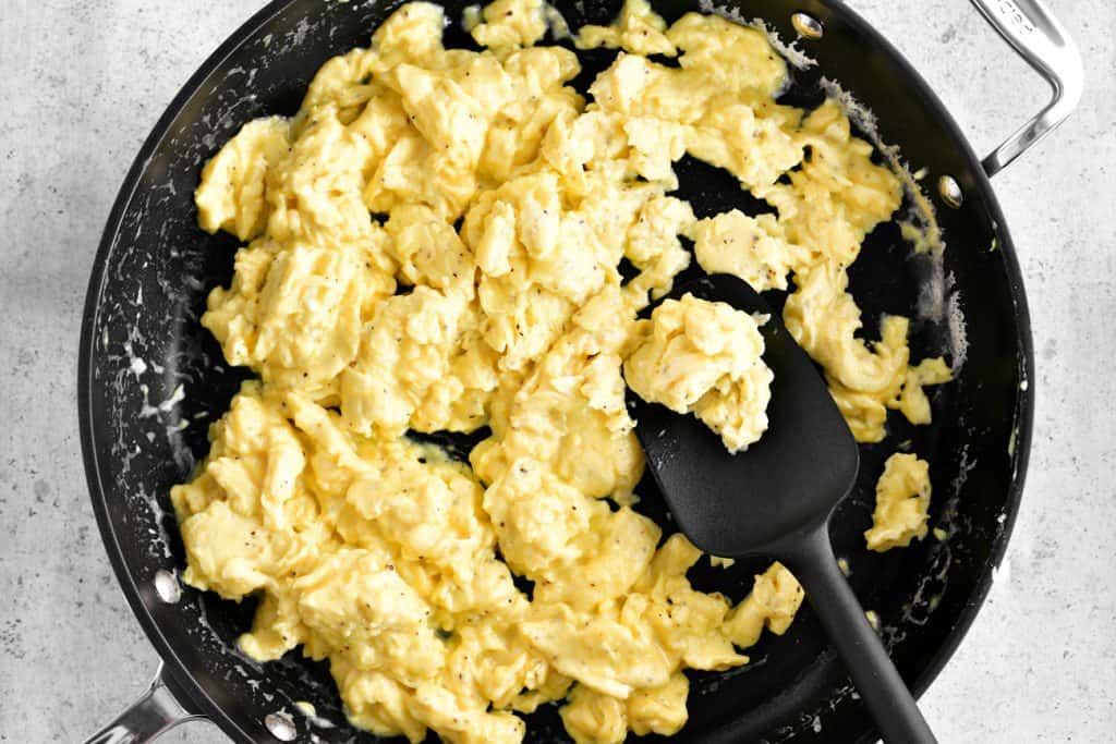 scrambled eggs in skillet with black spatula