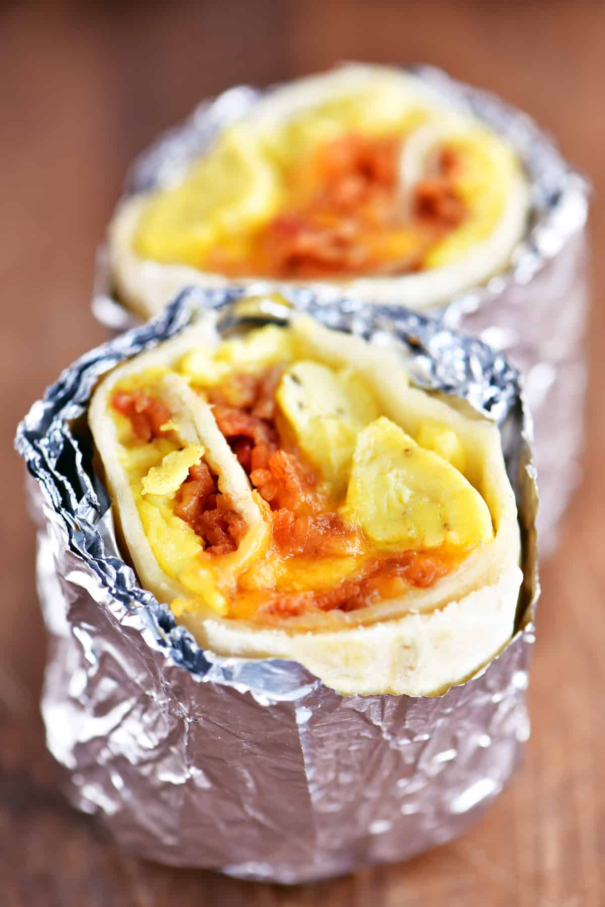 foil wrapped bacon egg and cheese breakfast burrito halved