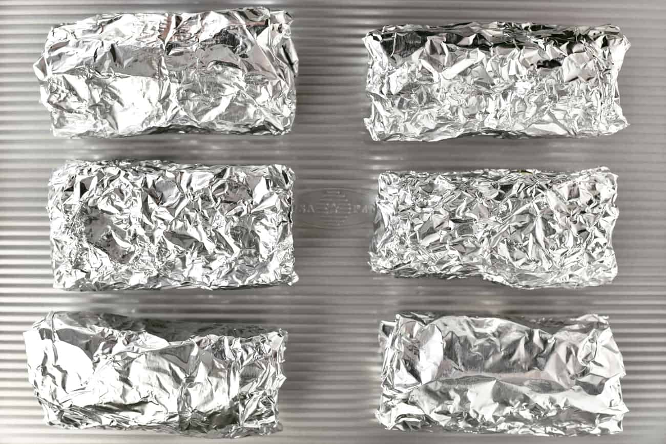 six foil wrapped breakfast burritos on a baking sheet