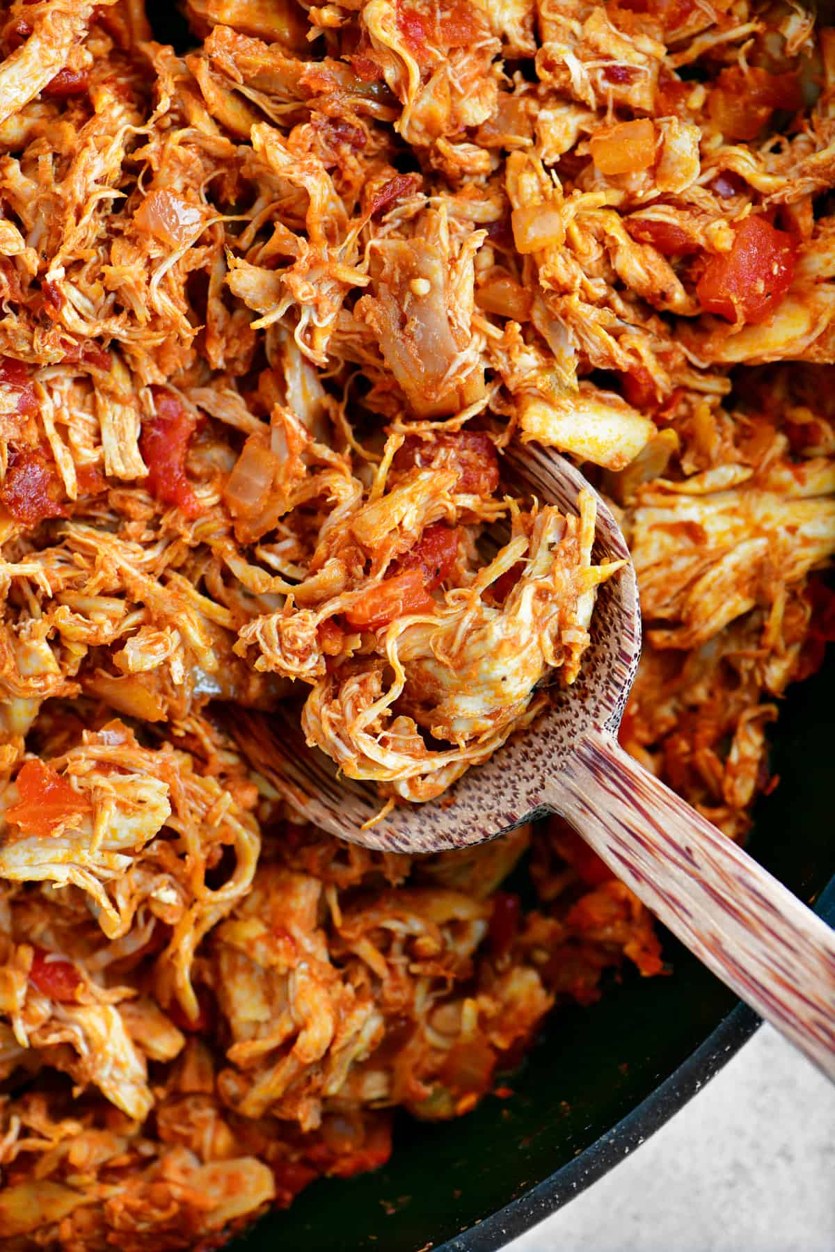Chicken Tinga and a wooden spoon in a skillet