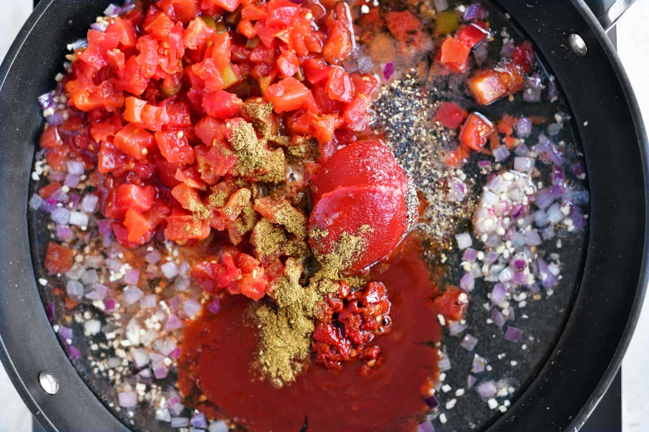 Peppers, onions, garlic, tomato paste and cumin in a frying pan