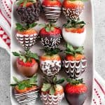 decorated chocolate covered strawberries on a white speckled platter