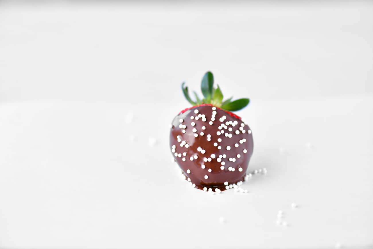 white sprinkles on a dipped strawberry