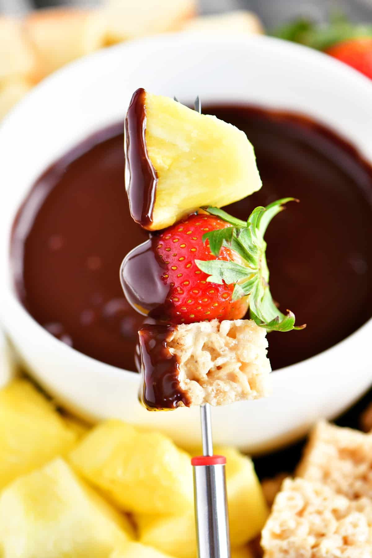 a rice crispy square, strawberry and pineapple speared on a fondue fork