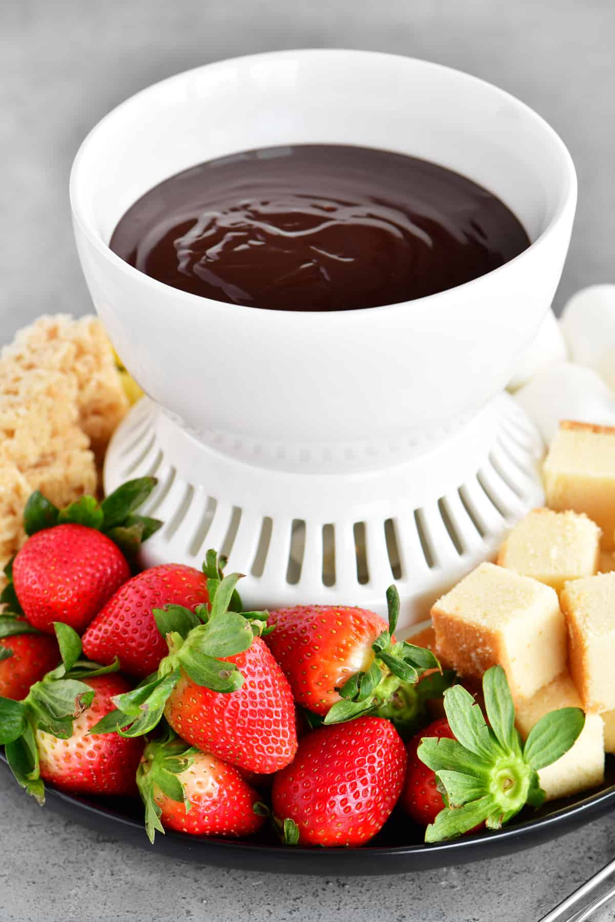 a fondue tray with strawberries and pound cake for dipping in chocolate