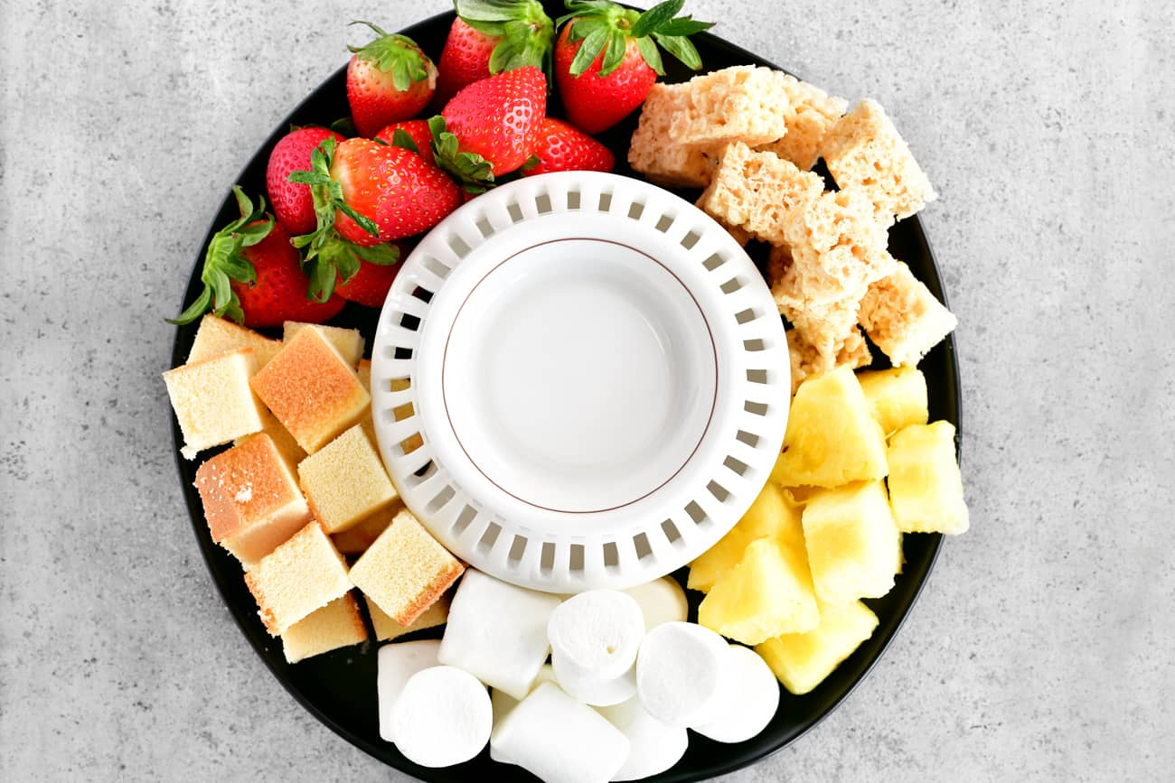 a fondue tray with fruit and sweet treats surrounding the bowl