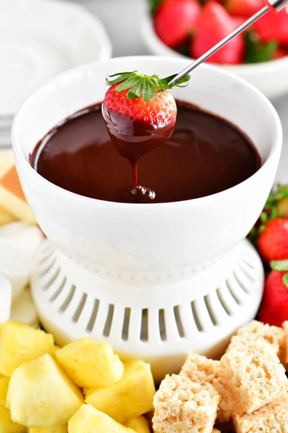 a strawberry being dipped into the chocolate fondue mixture
