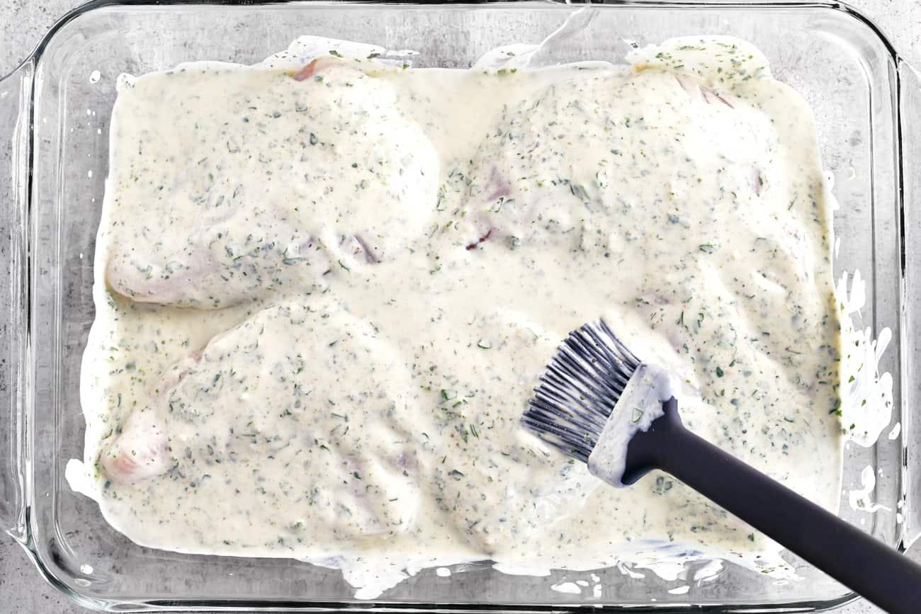 brushing yogurt and seasoning over the chicken breasts