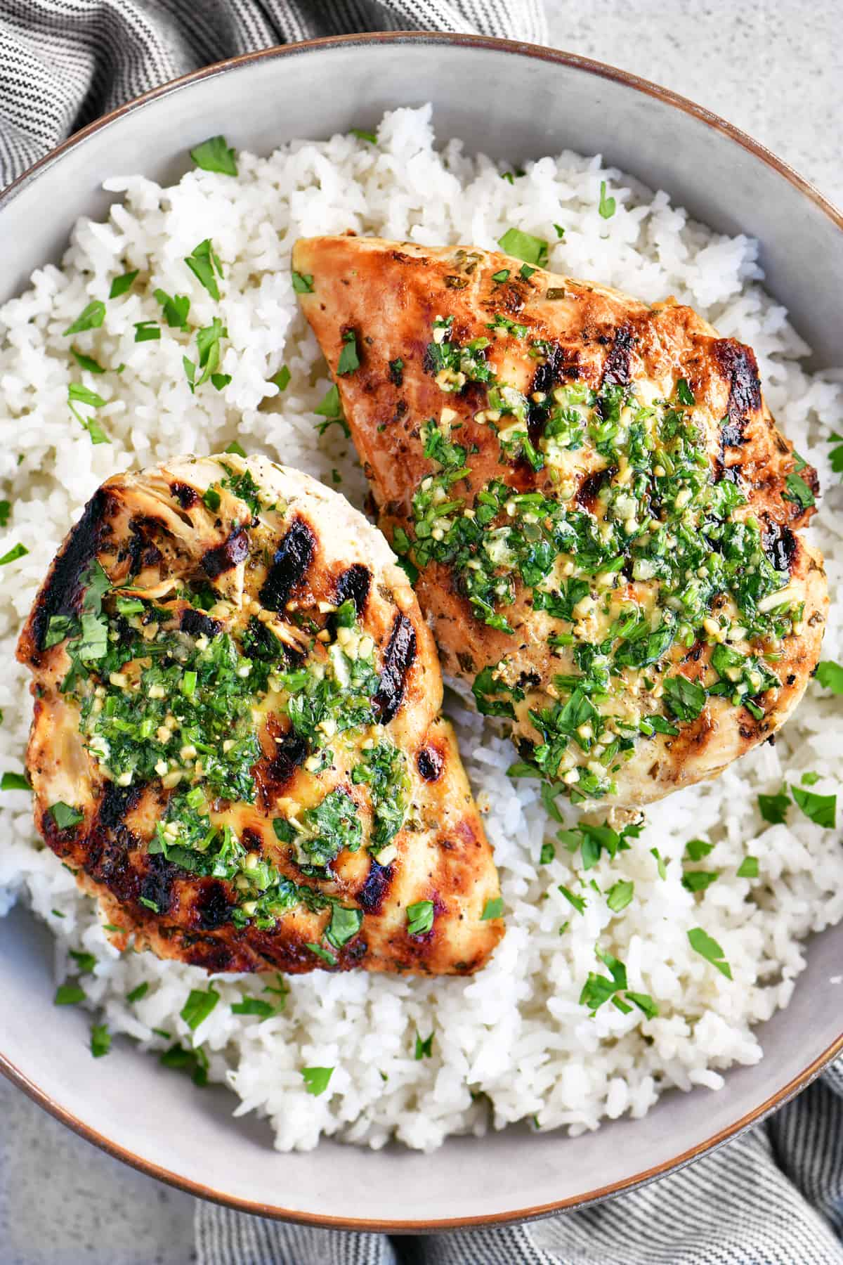 a photo of two cilantro-lime chicken breasts in rice
