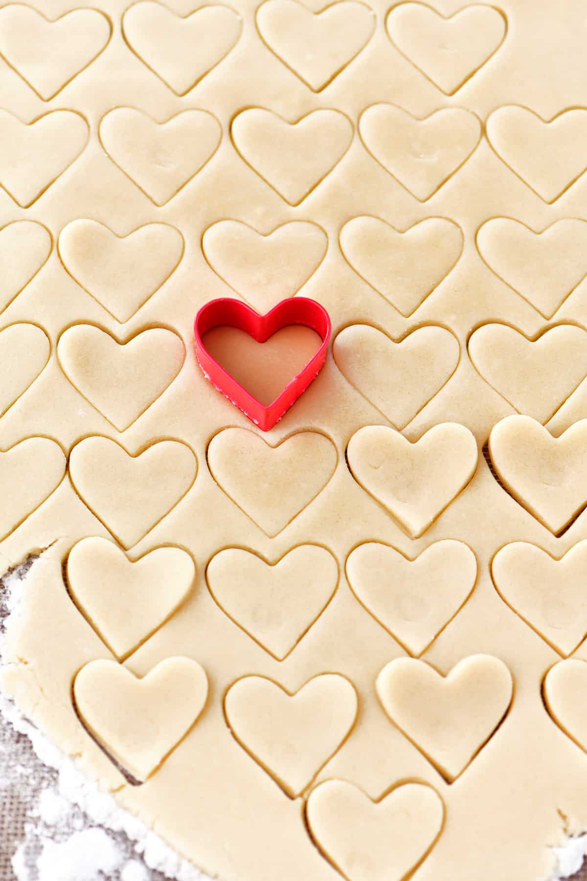 heart shaped cookie cutter cutting dough