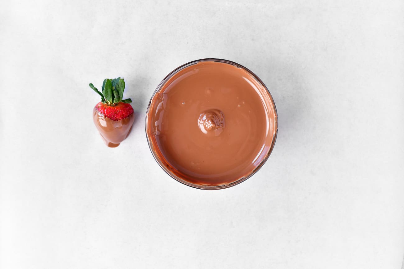 melted milk chocolate in a bowl and on a strawberry