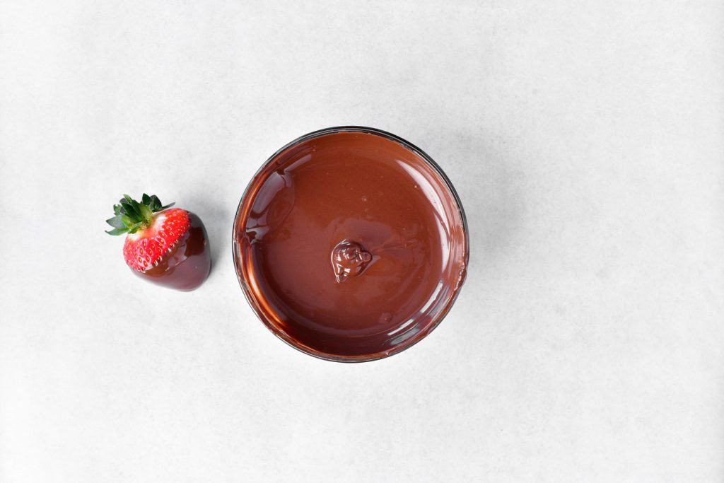 melted chocolate in a bowl and on a strawberry