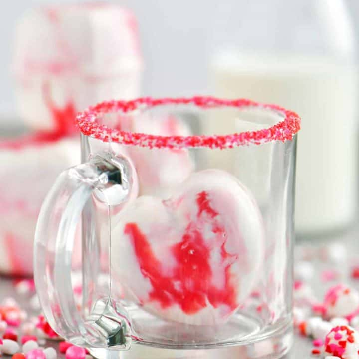 a heart shaped hot chocolate bomb in a glass cup