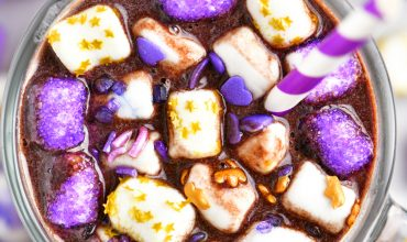 mug of hot chocolate with purple sprinkles on marshmallows