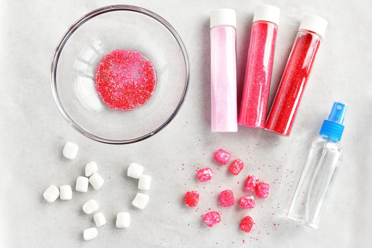 tubes of sprinkles, a bowl, mini marshmallows and a spray bottle