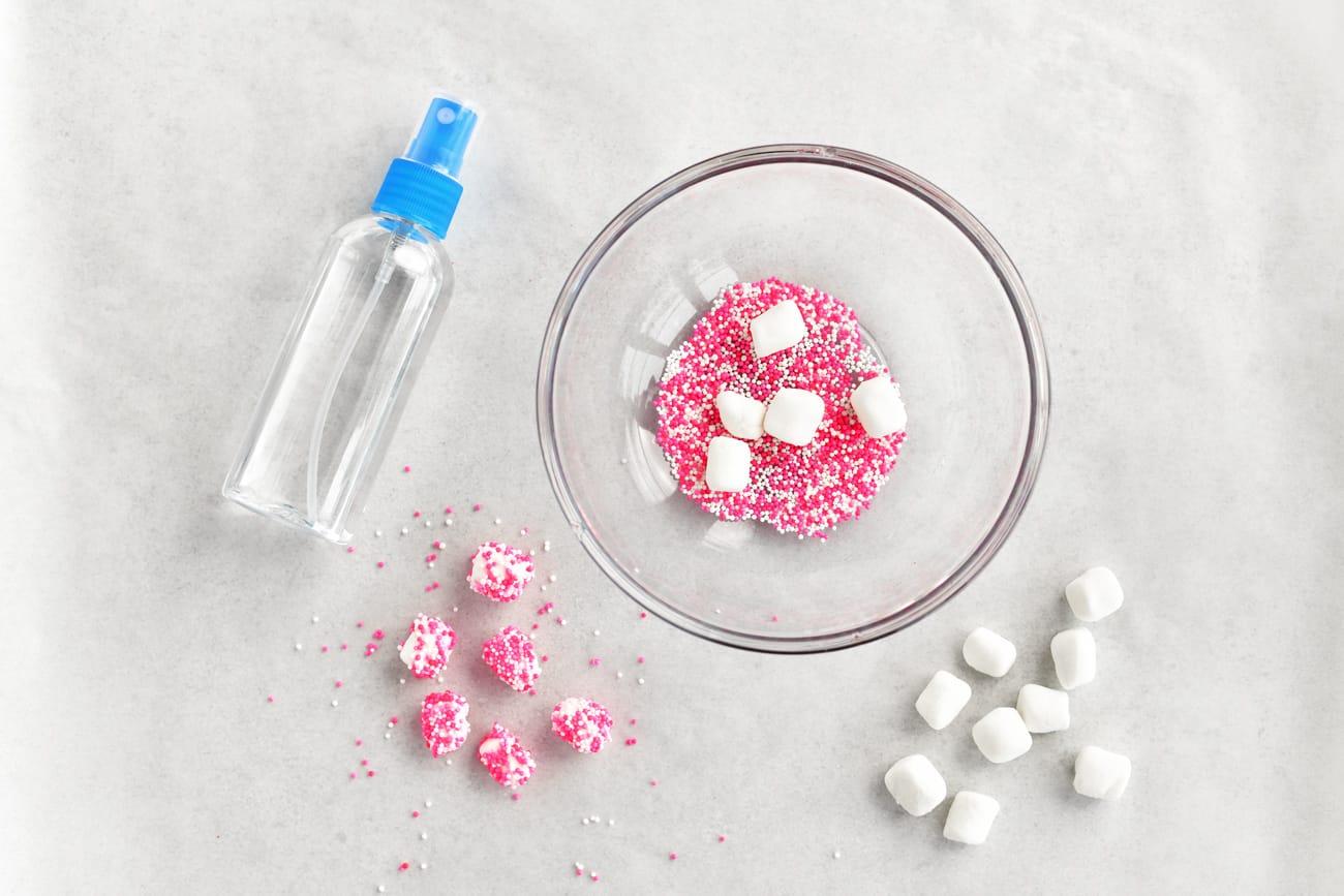 pink nonpareils in bowl, mini marshmallows, spray bottle