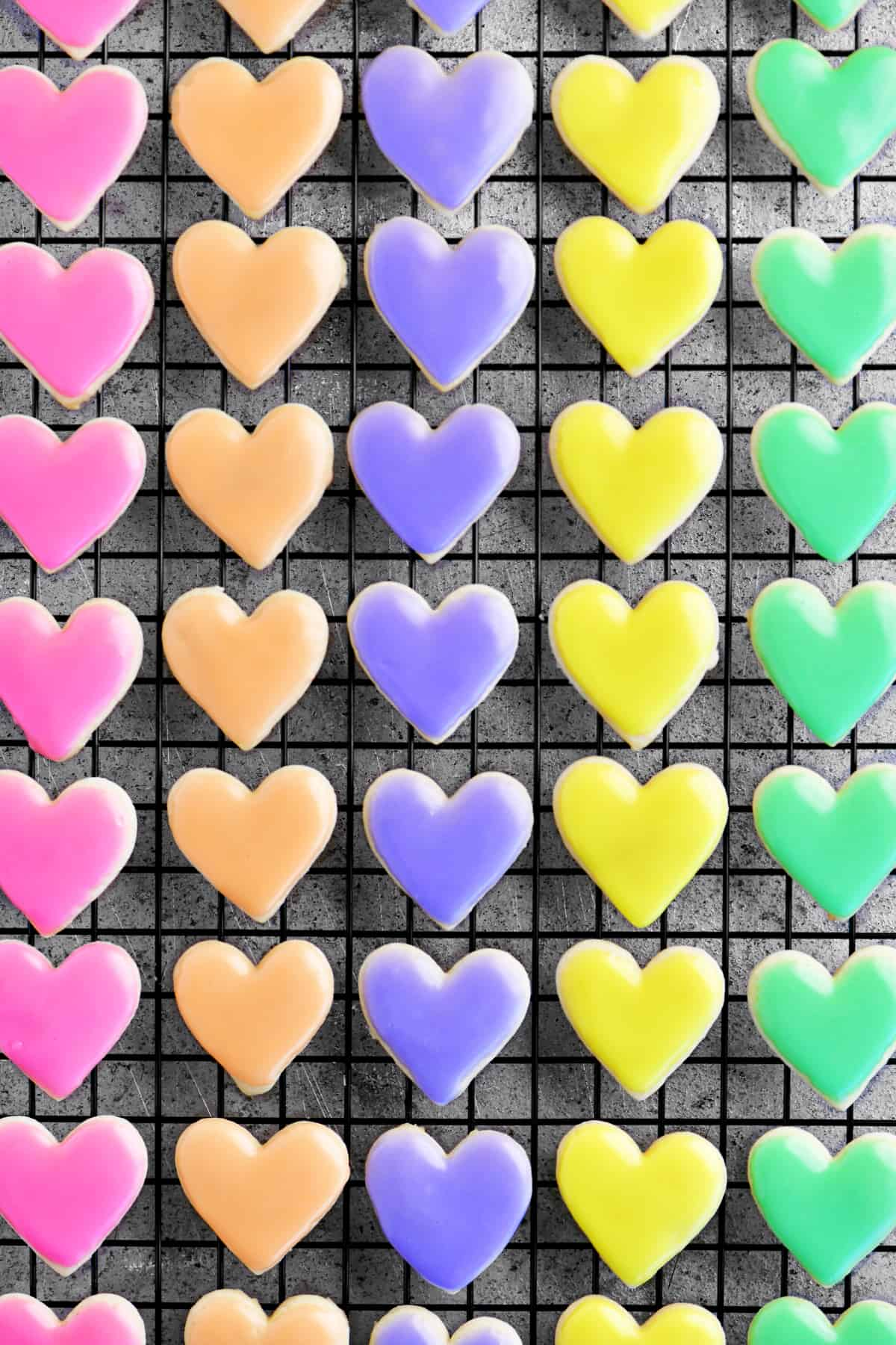 rows of colorful iced heart shaped sugar cookies
