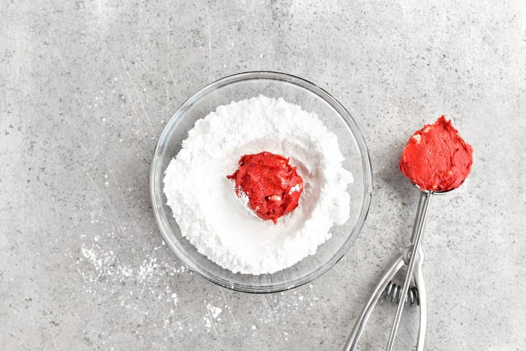 coating red velvet cookie dough balls with powdered sugar