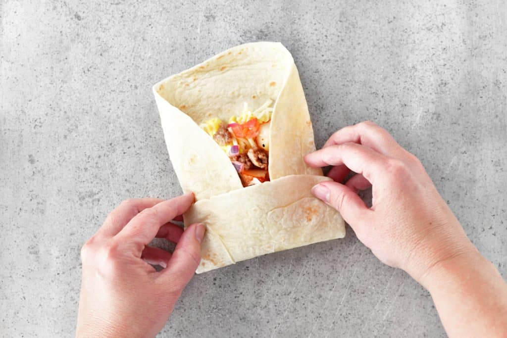 two hands folding a southwest breakfast burrito