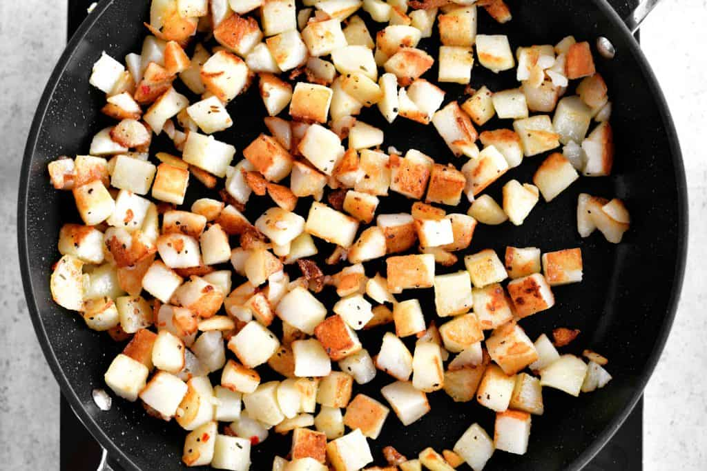 frying breakfast potatoes in a pan